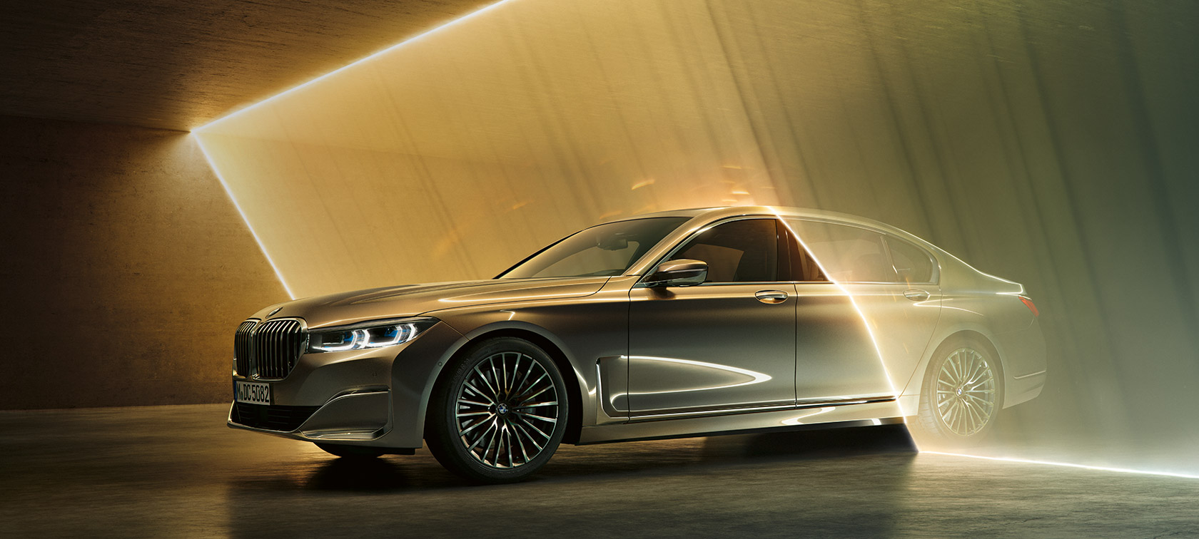 BMW 7 Series Sedan: grey BMW in three-quarter front view surrounded by beams of light